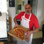Brian D'Millo holding a slice of pizza